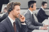 Photo handsome smiling young businessman in headset working in call center