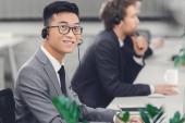 Fotografie pohledný mladý asijské podnikatel v headsetu se usmívá na kameru při práci v call centru