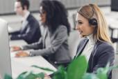 Fotografie boční pohled usměvavá mladá podnikatelka v headsetu, spolupráce s kolegy v call-centru