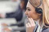 Photo side view of young female teleworker in headset smiling and working in office