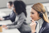 side view of smiling young woman in headset working with colleagues in office
