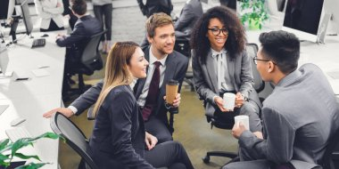 professional smiling young multiethnic businesspeople holding beverages and talking in office