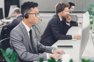 side view of young male call center operators working together in office