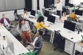 Blick aus der Vogelperspektive auf junge multiethnische Geschäftskollegen, die im Großraumbüro arbeiten und reden