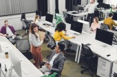 high angle view of young multiracial coworkers working and talking in open space office