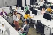 pohled z vysokého úhlu mladých mnohonárodnostní spolupracovníků, pracovat a mluvit v open space kanceláři