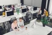 magas, szög, kilátás a fiatal munkatárs ül, és együtt dolgoznak, a nyitott terű munkahely