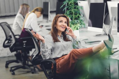 happy young businesswoman talking by smartphone and looking up in open space office