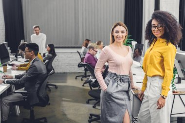 young multiethnic businesswomen smiling at camera while colleagues working behind in office