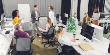 high angle view of professional young multiracial businesspeople working together in open space office