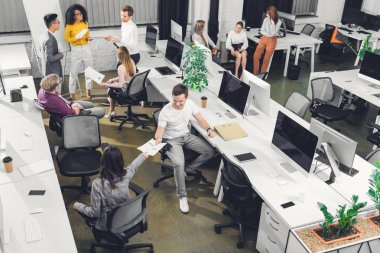 """Картина, постер, плакат, фотообои """"высокий угол обзора профессиональных молодых коллег, работающих с бумагами и компьютерами в открытом космосе """", артикул 236018888"""