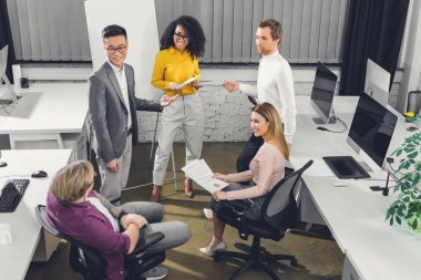 high angle view of multiethnic young businesspeople working together in office