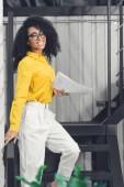 attraktive junge afrikanisch-amerikanische Geschäftsfrau hält Papiere in der Hand und lächelt in die Kamera im Büro