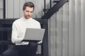 krásný usměvavý mladý muž sedí na schodech a používat přenosný počítač v kanceláři