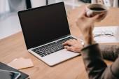 Fényképek vágott üzletasszony látképe a gépelés-on laptop munkahelyen csésze kávé