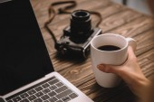 Fotografie cropped view of freelancer holding cup of coffee at workplace with vintage photo camera and laptop