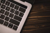 close up top view of laptop keyboard on wooden table