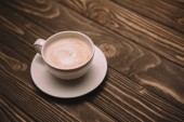 Fotografie white saucer and cup with cappuccino on wooden table