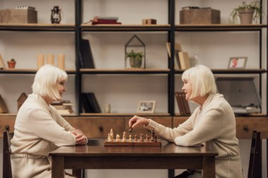 happy senior female twins playing chess together at home