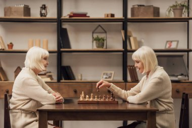 smiling senior female twins playing chess together in living room