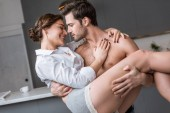 Fotografie passionate man holding in arms smiling girlfriend at home