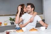 atraktivní žena, objímat a líbat tváře šťastný člověk u snídaně v kuchyni