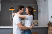 smiling couple looking at each other and hugging in kitchen