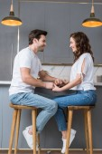 Fotografie happy couple sitting on chairs and holding hands in kitchen