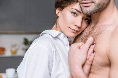 cropped view of man hugging with girlfriend at home