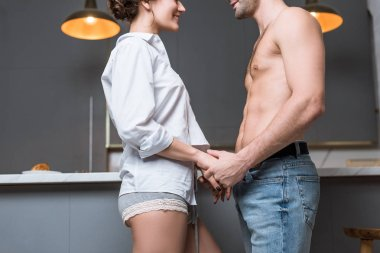 cropped view of young couple holding hands and looking into eyes