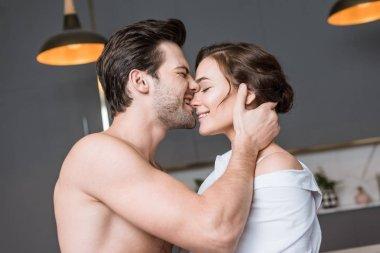 adult boyfriend biting girlfriend with closed eyes