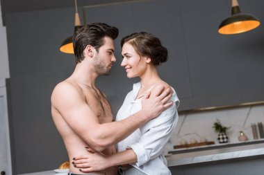 adult couple embracing and smiling at kitchen and looking into eyes