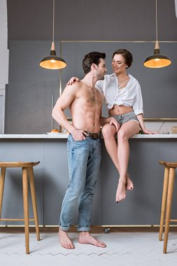 beautiful woman sitting on table and looking at handsome shirtless boyfriend in kitchen