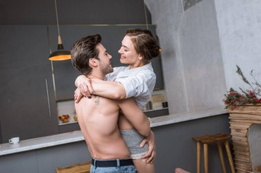 smiling couple hugging while standing in kitchen