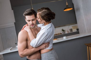 girlfriend hugging shirtless boyfriend while standing in kitchen