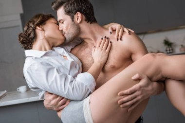 passionate man holding in arms and kissing girlfriend at home