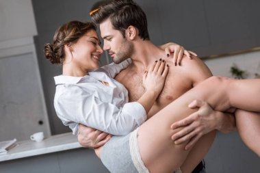 passionate man holding in arms smiling girlfriend at home
