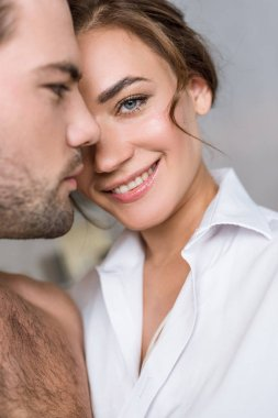 close up of attractive woman smiling near handsome boyfriend