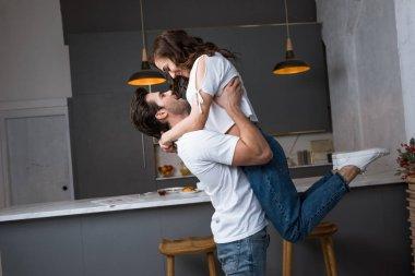 handsome man holding in arms attractive girlfriend in modern kitchen