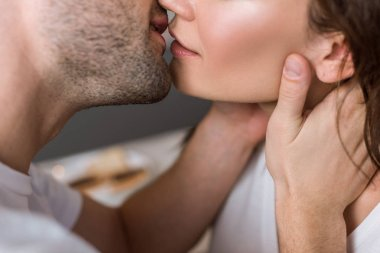 cropped view of man and woman kissing at home