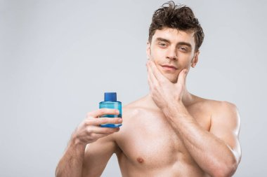 handsome shirtless man holding bottle with cologne, isolated on grey