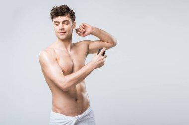 handsome shirtless man spraying deodorant, isolated on grey
