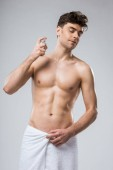 shirtless sexy Mann sprühen Parfüms, isoliert auf grau