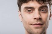 portrét pohledný mladý, usměvavý muž izolované Grey