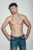 sexy stylové svalů macho v džínách pózuje na grey