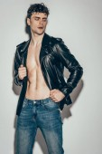 handsome sexy rocker posing in jeans and black leather jacket on grey