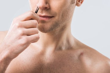 cropped view of man plucking hair with tweezers from nose, isolated on grey