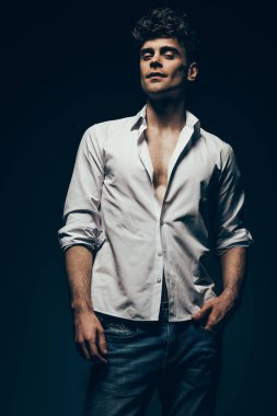fashionable sexy man posing in white shirt isolated on dark grey