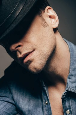 portrait of handsome man posing with hat isolated on dark grey