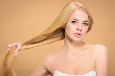 Pretty girl holding long straight hair on beige background